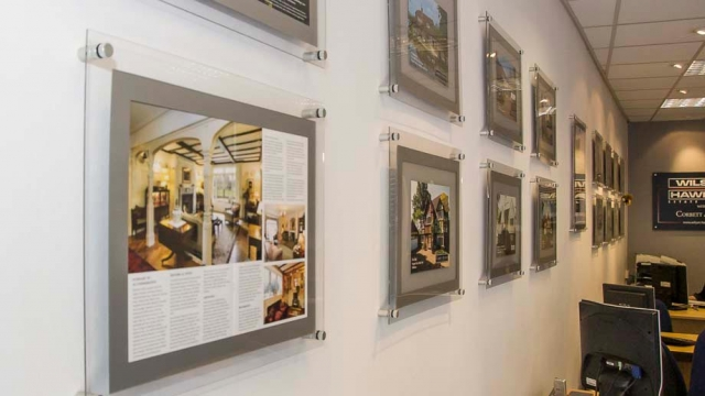 Series of wall mounted A3 poster holder displays in estate agents for property marketing.