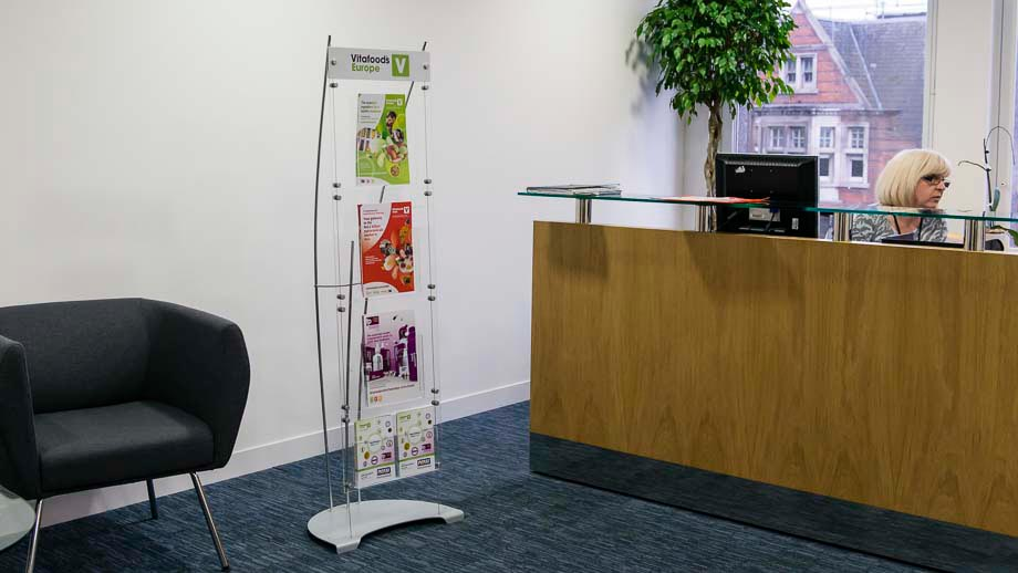 Floor standing brochure dispenser stand with A4 and A5 acrylic pockets in office reception area